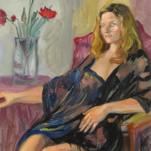 A girl wearing a black chemise is seating next to a vase of poppies