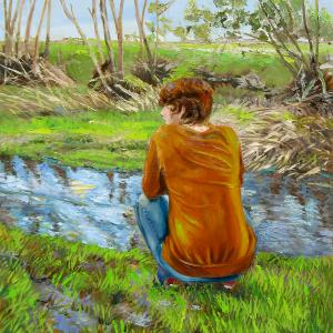 A young woman is seen from the back, crouching in nature in front a creek