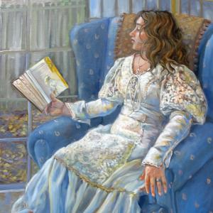A young lady wearing a white dress is sitting with a book in her hand.