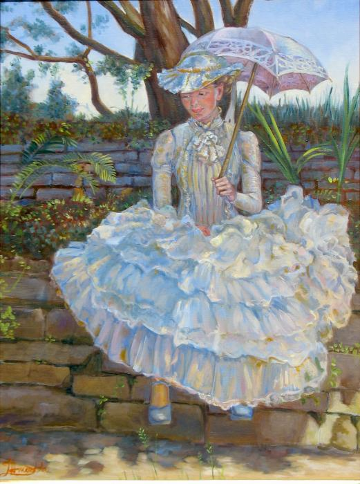 A girl dressed in a white chiffon dress is sitting on a stone wall.