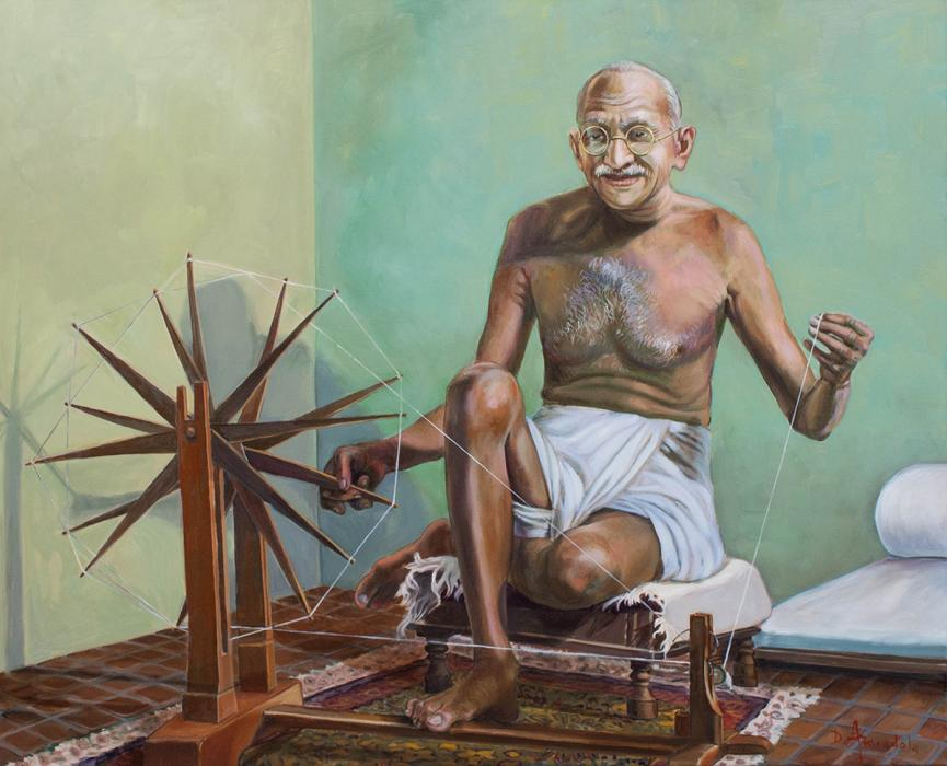Gandhi is sitting in front of the spinning wheel, making cloth, in his room