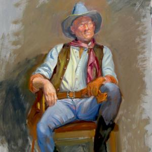 Cowboy sitting down after a hard day's work.