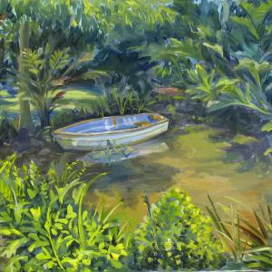 A small boat is resting in a small pond among shrubs and tall grass of all sort.