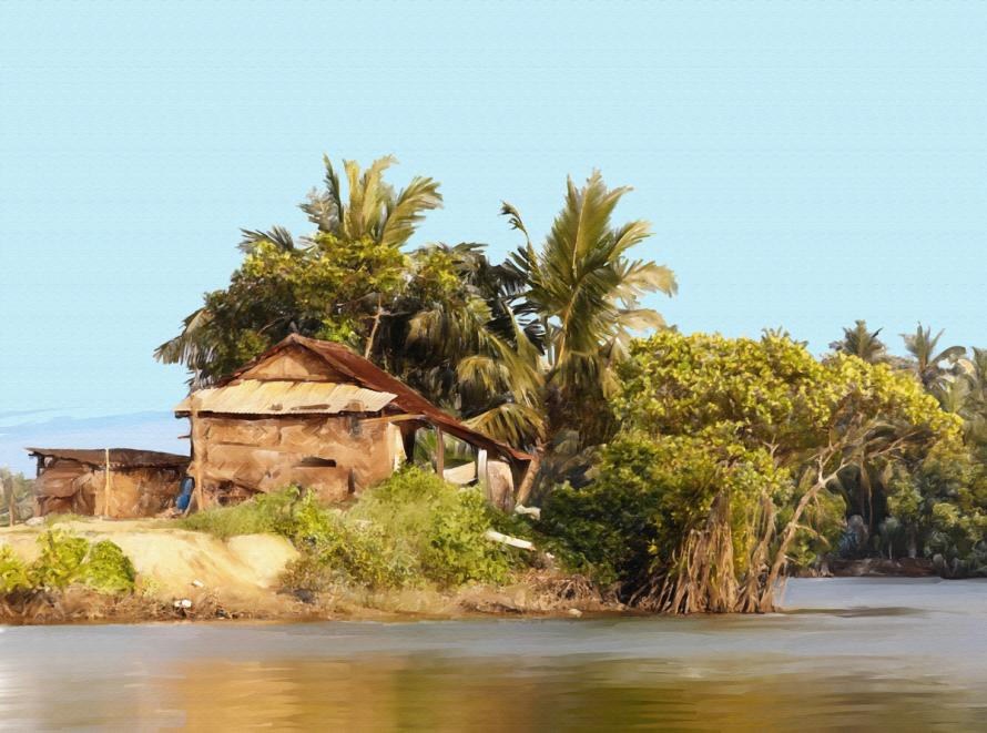 A grass hut in India with a river in front.