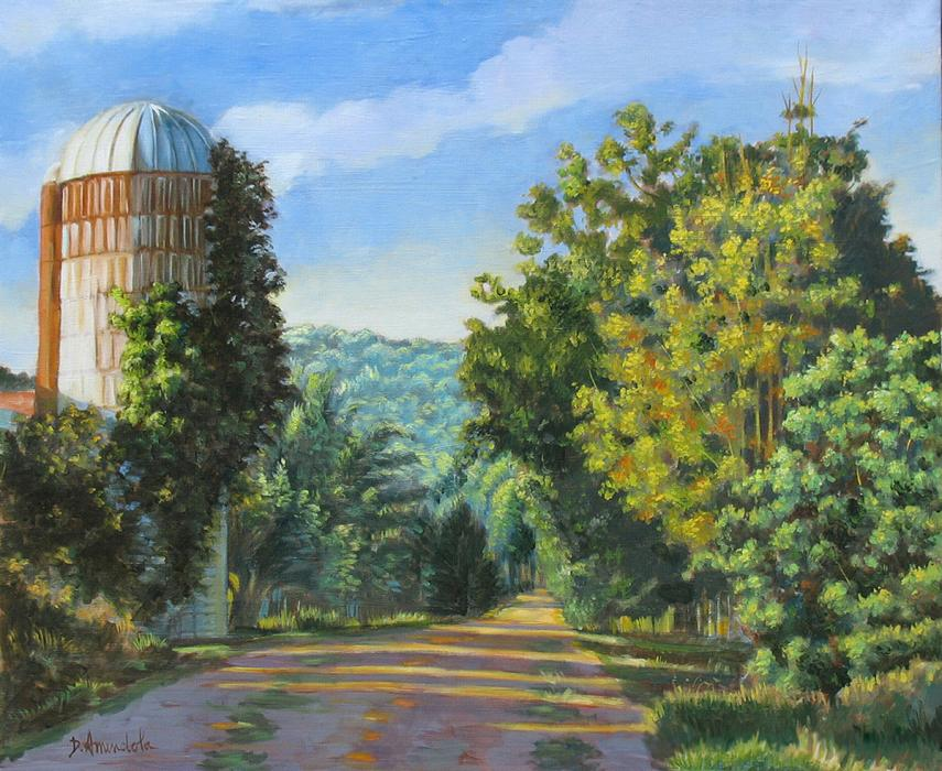 A dirt road is bordered with trees on each side with a silo on the left.